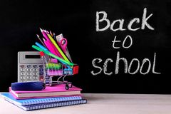 kleurrijk schoollevering en het winkelen karretje op de achtergrond van de schoolraad met de woorden terug naar school royalty-vrije stock foto