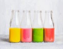 Kleurrijk smoothiesassortiment in glasflessen op lichte lijst, zijaanzicht Stock Fotografie