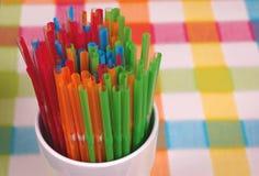 Kleurrijk stro in wit glas op geruite mat royalty-vrije stock foto's