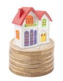 Kleurrijk stuk speelgoed huis op stapel euro muntstukken Stock Afbeeldingen