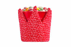 Kleurrijk suikergoed in een rode die emmer met stoffenkroon wordt verfraaid Stock Afbeelding