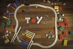Kleurrijk van het jonge geitjesspeelgoed kader als achtergrond met veel speelgoed op houten vloerachtergrond Hoogste mening Vlak  Stock Fotografie