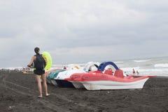 Kleurrijk van pedalo die op het strand, bewolking, wolken, golven wordt geparkeerd Meisje op het strand royalty-vrije stock foto