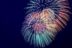 Kleurrijk vuurwerk op de donkere achtergrond van de dluehemel Stock Foto
