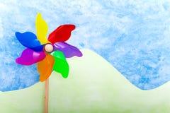 Kleurrijk windmolenstuk speelgoed op groene heuvels royalty-vrije stock fotografie