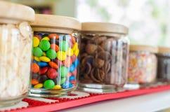 Kleurrijk zoet suikergoed in fles op plank in dessertopslag stock afbeelding
