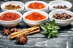 Kleurrijke aromatische Indische kruiden en kruiden op een oude eiken houten diepe blauwe raad Stock Foto's