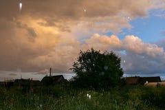 Kleurrijke avondhemel en kleine hagel na onweersbui over vill Royalty-vrije Stock Foto's