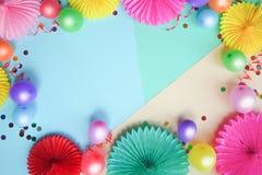 Kleurrijke ballons en document bloemen op de blauwe mening van de lijstbovenkant Feestelijke of partijachtergrond vlak leg stijl  stock fotografie