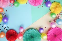 Kleurrijke ballons en document bloemen op kleurentabel hoogste mening Feestelijke of partijachtergrond vlak leg stijl stock foto