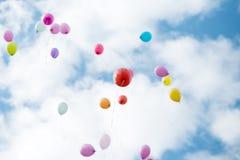 Kleurrijke baloons die in blauwe bewolkte hemel vliegen stock afbeelding