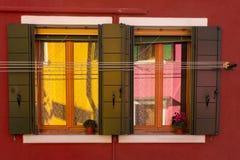 Kleurrijke bezinningen in een venster op Burano stock fotografie