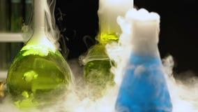 Kleurrijke biologische en vloeistoffen die, ondergronds laboratorium, chemie koken roken stock footage