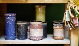 Kleurrijke blikken van verf op de plank in de workshop Stock Foto