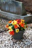 Kleurrijke bloemen buiten grafsteen Stock Foto's