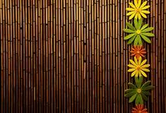 Kleurrijke bloemen en bamboemuur stock afbeeldingen