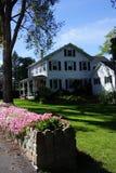 Kleurrijke bloemen en het klassieke huis van New England Stock Afbeelding