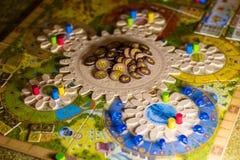 Kleurrijke boardgame met tandraderen, beeldjes, spaanders en speelkaarten stock fotografie
