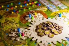 Kleurrijke boardgame met tandraderen, beeldjes, spaanders en speelkaarten stock foto