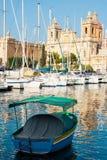 Kleurrijke boot en meningsst Lawrence ` s Kerk, Isla, Malta Stock Foto's