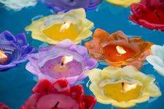 Kleurrijke brandende kaarsen die op water drijven stock foto