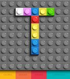 Kleurrijke brief T van de bouw van legobakstenen op grijze legoachtergrond Legobrief M stock illustratie