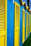 Kleurrijke cabines en strandparaplu's door het overzees stock afbeeldingen