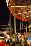 Kleurrijke carrouselpaarden bij de Kerstmismarkt op Rood Vierkant tegen de achtergrond van Moskou het Kremlin in de avond stock afbeelding