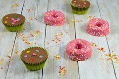 Kleurrijke chocoladecakes op houten lijst en suikersterren stock afbeeldingen