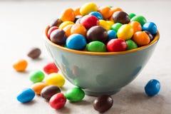 Kleurrijke chocoladeknopen in kom op grijze steenachtergrond stock fotografie