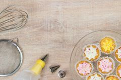Kleurrijke cupcakes en bakselhulpmiddelen op een houten lijstachtergrond Royalty-vrije Stock Afbeeldingen