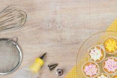 Kleurrijke cupcakes en bakselhulpmiddelen op een houten lijstachtergrond Royalty-vrije Stock Fotografie