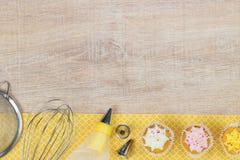 Kleurrijke cupcakes en bakselhulpmiddelen op een houten lijstachtergrond Stock Fotografie
