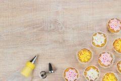 Kleurrijke cupcakes en bakselhulpmiddelen op een houten lijstachtergrond Royalty-vrije Stock Foto's