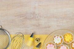 Kleurrijke cupcakes en bakselhulpmiddelen op een houten lijstachtergrond Stock Foto's