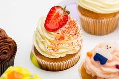 Kleurrijke cupcakes met verschillende Smaken De aardbei Cupcake is in het centrum mooie cakes op witte lijst Sluit omhoog Royalty-vrije Stock Fotografie