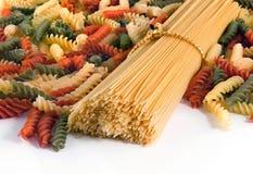 Kleurrijke de chef-kokbos van spaghettideegwaren die op witte achtergrond wordt ge?soleerd De close-up van deegwaren stock foto