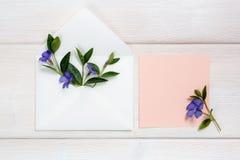 Kleurrijke de zomerbloemen in envelop en roze blad op houten achtergrond Royalty-vrije Stock Afbeelding
