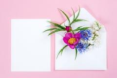 Kleurrijke de zomerbloemen in envelop en wit blad op roze achtergrond Stock Afbeelding