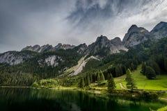 Kleurrijke de zomerscène van het zijmeer van Vorderer Gosausee met bos en rotsachtige heuvels bij achtergrond in Oostenrijk royalty-vrije stock afbeeldingen