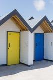 Kleurrijke deuren van geel en blauw, met elke één die, witte strandhuizen individueel worden genummerd op een zonnige dag Stock Foto's