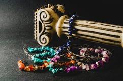 Kleurrijke die armbanden van natuurstenen en antieke kolom op grijze achtergrond worden gemaakt royalty-vrije stock afbeelding