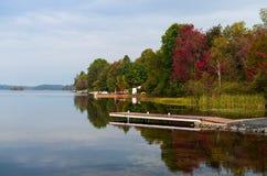 Kleurrijke die bomen in een kalm meer worden weerspiegeld stock foto