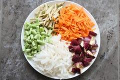 Kleurrijke die groenten in plaat met grijze achtergrond worden geschikt Royalty-vrije Stock Afbeeldingen