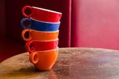 Kleurrijke die koffiekoppen op een oude houten lijst in een koffie worden gestapeld Royalty-vrije Stock Foto