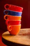 Kleurrijke die koffiekoppen op een oude houten lijst worden gestapeld Royalty-vrije Stock Foto