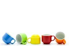 kleurrijke die koffiekoppen op witte achtergrond worden geïsoleerd Stock Foto