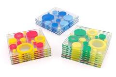 Kleurrijke die onderleggers voor glazen voor glas op wit worden geïsoleerd Stock Foto