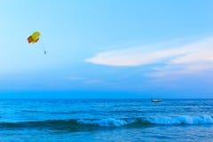 Kleurrijke die parasailvleugel door boot in het zeewater wordt getrokken Stock Afbeeldingen