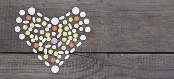 Kleurrijke die pillen in hartvorm worden geschikt op houten achtergrond stock fotografie
